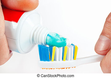 Hand squeezes toothpaste on the toothbrush on a white...