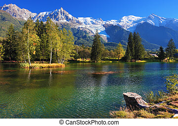 Lake with cold water surrounded by trees and snow-capped...