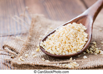 Wooden Spoon with Minced Almonds (on rustic background)