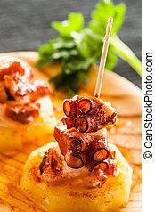Octopus tapas - Spanish octopus tapas on a wooden dish.