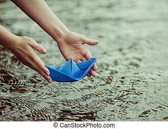 paper boat - hands of a young woman with a paper boat by the...