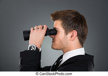 Side View Of Businessman Looking Through Binoculars