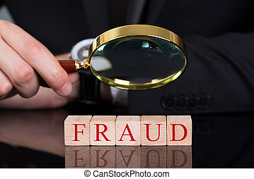 Businessman Examining Fraud Blocks Through Magnifying Glass...