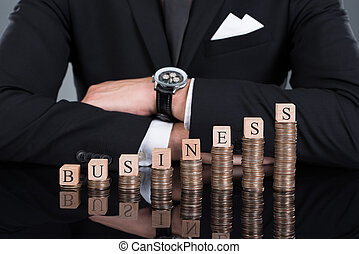 Businessman With Business Blocks On Stacked Coins -...