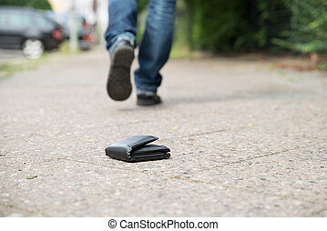 Man Walking Against Fallen Wallet On Street - Low section of...