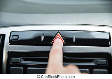 Hand Pressing Emergency Stop Button In Car - Closeup of...