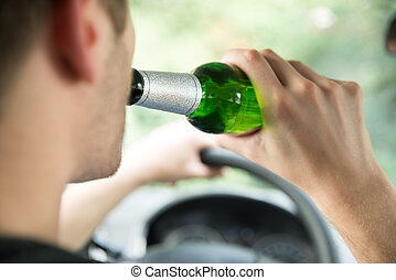 Man Drinking Alcohol While Driving Car - Cropped image of...