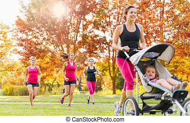 Mother and friends jogging - Woman pushing her little girl...
