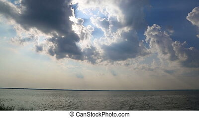 beautiful landscape with clouds and sunlight over lake -...