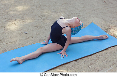 Little gymnastics girl stretching outdoors