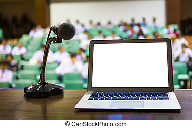 Laptop and microphone on the rostrum in empty conference...