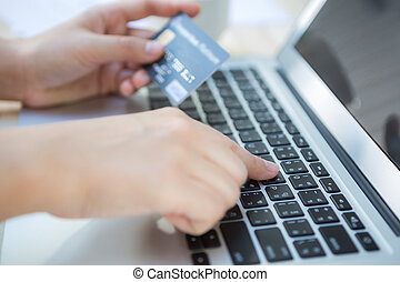 Hands holding a credit card and using laptop computer for...