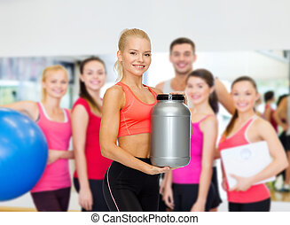 smiling sporty woman with jar of protein - fitness and diet...