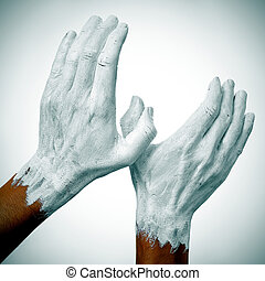 dove of peace - the hands of a man painted in white forming...