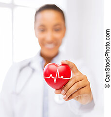 female doctor holding red heart with ecg line - healthcare...