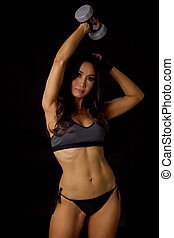 Athletic asian woman lifting the dumbbells