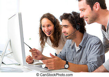 Group of people working around a computer