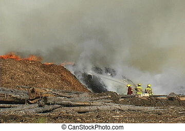 Fire in a cedar waste pile next to lumber mill
