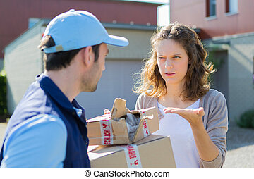 Young attractive woman angry against delivery man - View of...