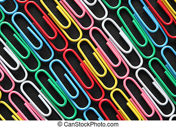 Diagonal rows of colorful paper clips on black card