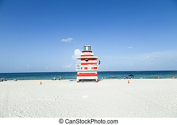 People enjoying the beach with lifeguard tower