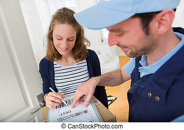 Young attractive woman signing on delivery paper - View of a...