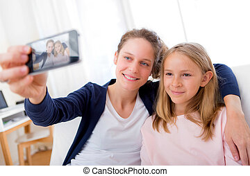 Attractive woman and little sister taking selfie - View of...