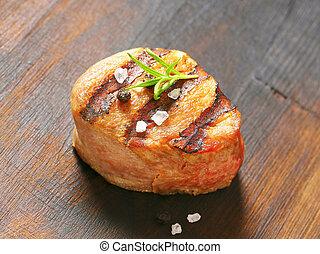 Grilled pork medallion on wood
