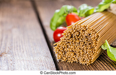 Wholemeal Spaghetti (close-up shot) on an old wooden table