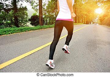 young fitness woman running on forest road
