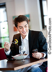 Man with Salad and Phone - A young and attractive man uses...