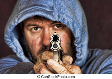 Thief or gang member holding a handgun in a threatening...