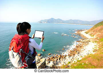 woman hiker use digital tablet - hiking woman sit on seaside...