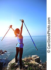 cheering hiking woman stand seaside rock looking the view...