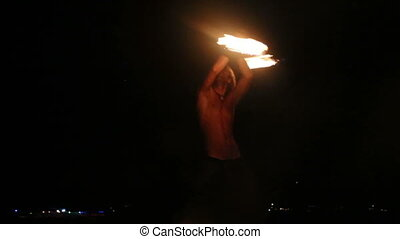 Male Artist of the spins fire poi on a rock at night