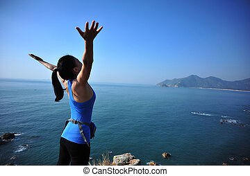 cheering woman hiker stand seaside rock looking the view...