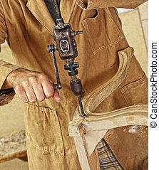carpenter with hand drill - detail of caucasian carpenter at...