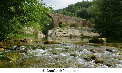 Mountain river with medieval stone bridge in Pyrenees...