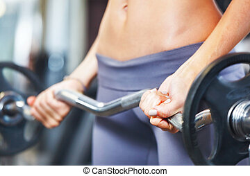 Young woman exercising with barbell in gym.