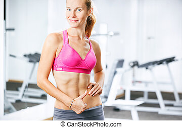 Portrait of happy athletic woman in gym showing thumb up.