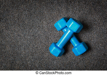 Small dumbbells on floor - fitness concept.