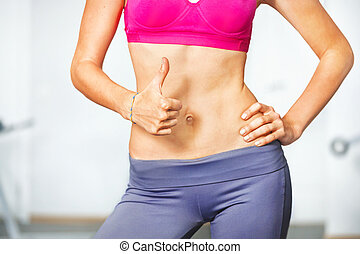 Closeup of young slim woman with six-pack torso.