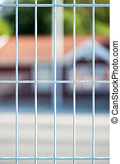 Closeup of a metal fence with blurred red house in...