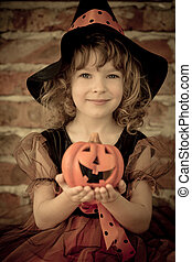 Halloween - Funny child dressed witch costume holding...