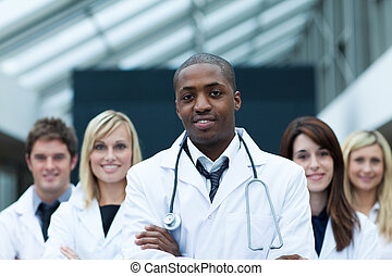 Afro-American doctor leading his team with folded arms and...