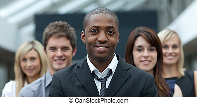 Afro-American businessman smiling at the camera with his team