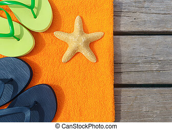 Beach slippers, towel and starfish on wood background...