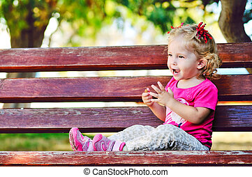 ?ute toddler on the bench - ?ute toddler girl sitting on the...