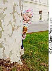 peekaboo - toddler girl hiding behind the tree