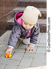 toddler girl playing toy car